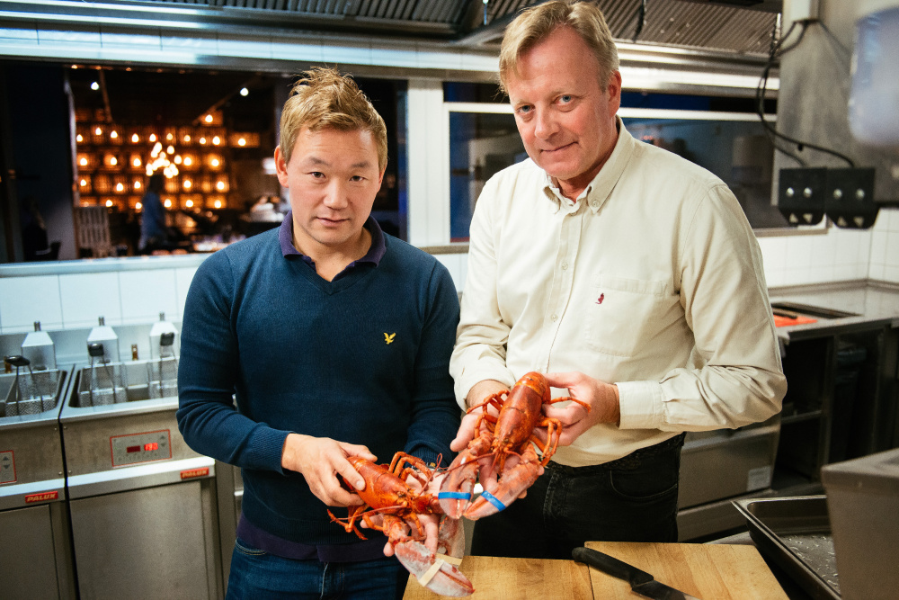 """Thomas Dahlstedt, left, who co-owns and manages Stockholm's Burger & Lobster, and Chef Anders Westerholm hold cooked North American lobsters. A proposed import ban is """"too dramatic,"""" Westerholm said."""