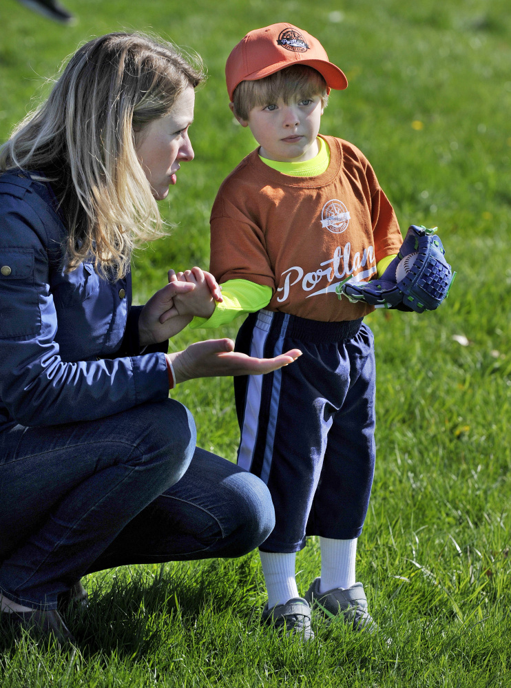 Erin Yarema tries to coax her son, 4-year-old Nicholas Yerema, to go play with teammates as they were getting ready for the Little League Opening Day ceremonies Saturday. Yarema plays for Deering Memorial Post 6859.