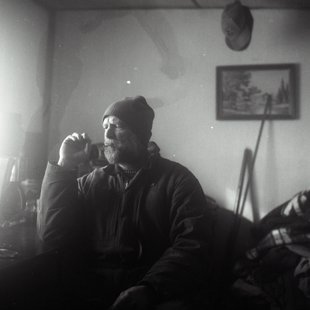Jess McBreairty, the subject of an undercover sting by Maine Game Wardens, smokes a hand rolled cigarette as he wakes up in his trailer in Allagash Sunday, February 14, 2016. McBreairty lives in poverty, eating many meals at friends' homes just to get by. This was photographed with black and white film on a Rolleiflex camera.