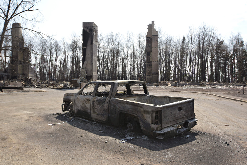 A charred truck sits near burned structures in the neighborhood of Abasand in wildfire-ravaged Fort McMurray, Alberta, on Friday. Jason Franson /The Canadian Press via AP