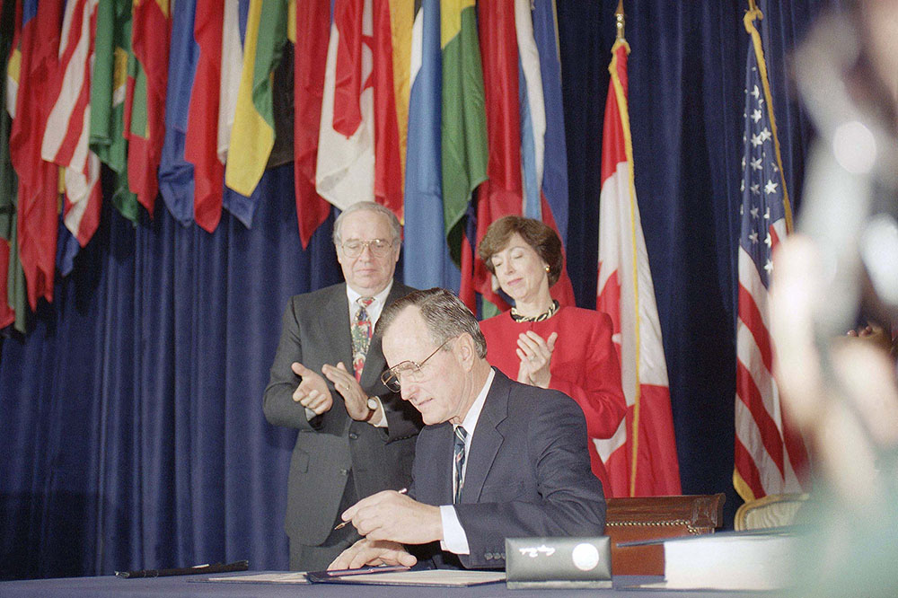 President George H. W. Bush signs the North American Free Trade Agreement during a ceremony at the Organization of American States headquarters on  Dec. 17, 1992, in Washington, D.C. Canadian Ambassador. Derek Burney and U.S. Trade Representative Carla Hills applaud. The president predicted an explosion of growth throughout North America as he signed the agreement. The Associated Press