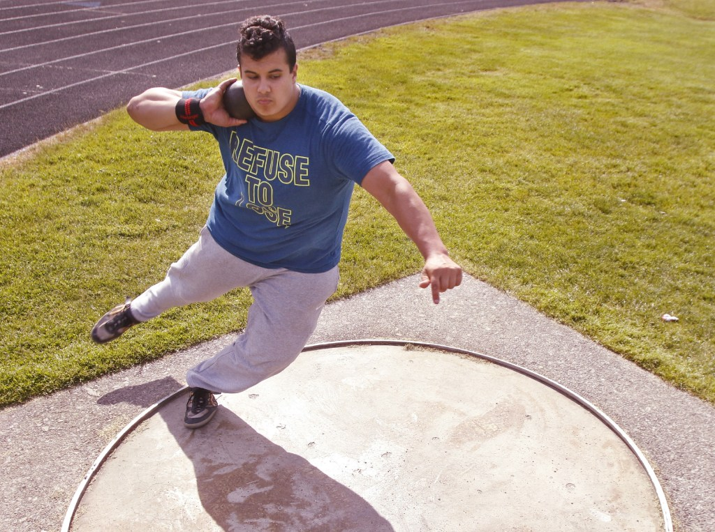 Dan Guiliani practices shot put at South Portland High School on Thursday. With a throw in May, he broke the New England record by almost 4 feet. Gregory Rec/Staff Photographer)