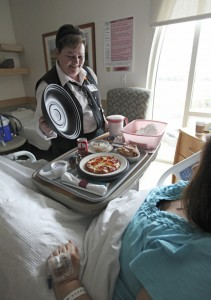 Beth Loney, a service assistant at Mercy Hospital, serves lunch to a patient.