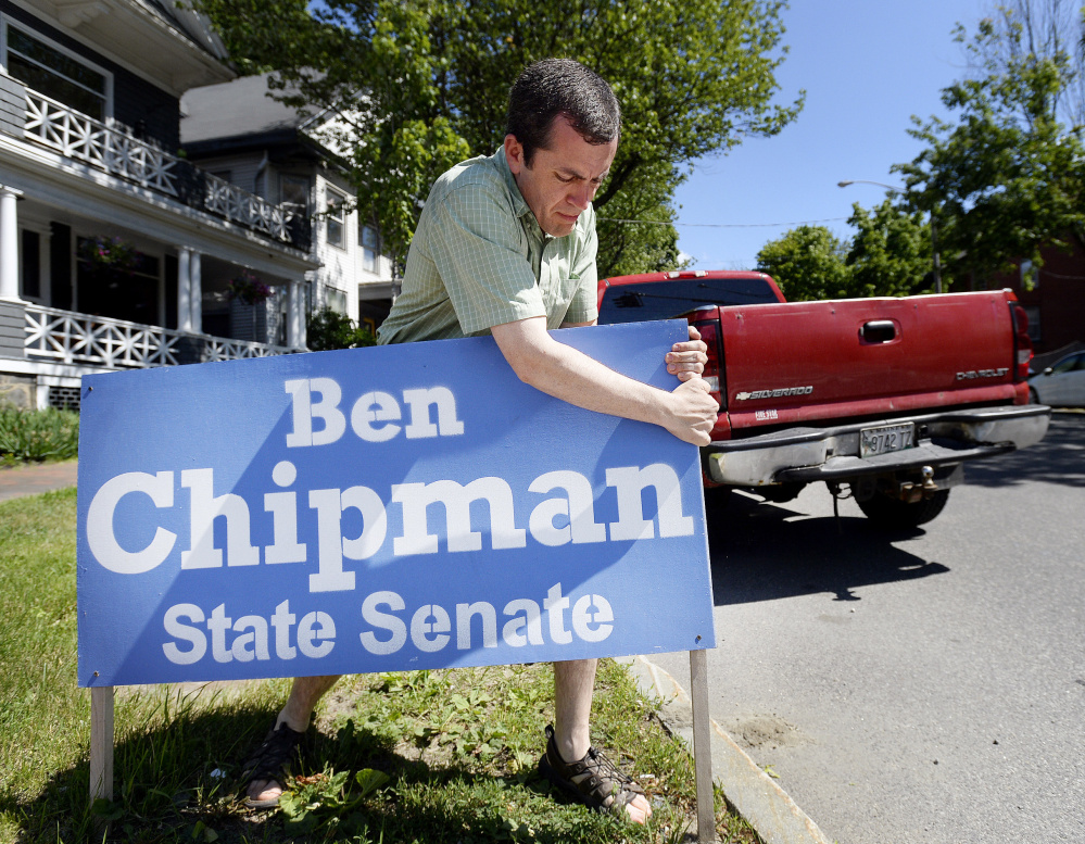 State Rep. Ben Chipman, who won the Democratic primary in Senate District 27 on Tuesday, removes a campaign sign on State Street in Portland. The hard-fought three-way race sparked ethics complaints.