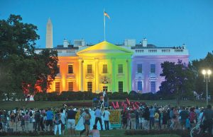 PEOPLE GATHER IN WASHINGTON'S LAFAYETTE PARK on June 26, 2015, to see the White House illuminated with rainbow colors to mark the U.S. Supreme Court's ruling to legalize same-sex marriage.