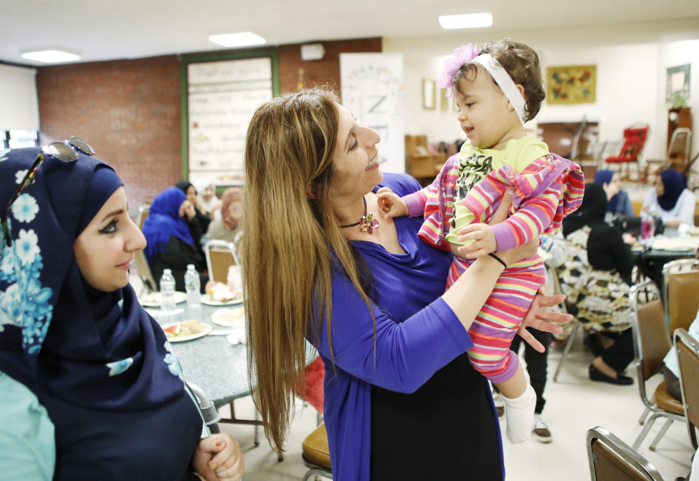Zoe Sahloul, executive director of the New England Arab American Organization, center, greets 1-year-old Annabella Al Shaar as the child's mother, Oula Al Shaar, looks on during the Eid-al-Fitr celebration Saturday in Westbrook. Hundreds attended the event.