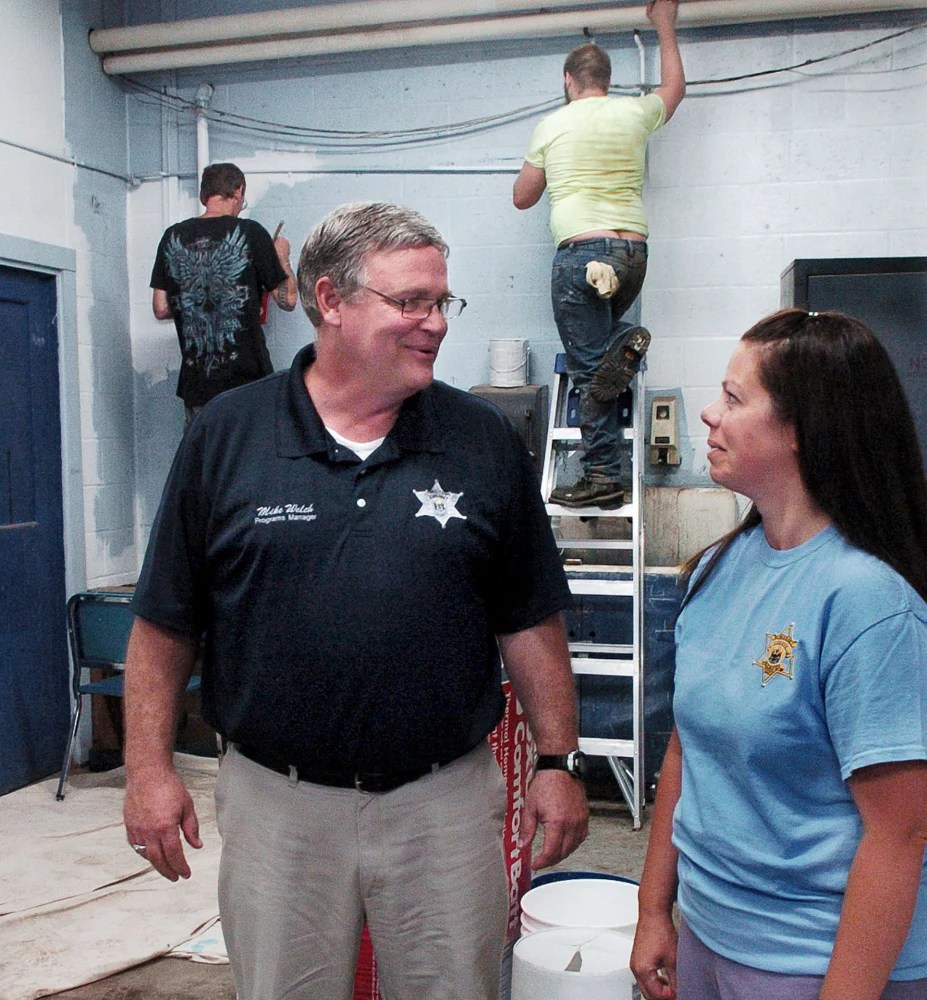 Somerset County Jail Programs Manager Mike Welch speaks with Community Corrections Program Supervisor Teresa Brown as participants in a community service program paint walls at Madison Junior High School.
