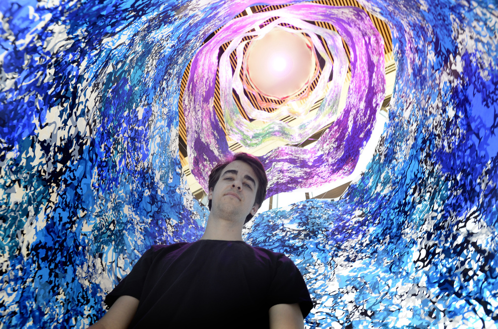 """Carter Shappy inside his cylindrical """"Colorcosm"""" at Bigelow Laboratory for Ocean Sciences in East Boothbay. The 20-foot-high print emulates an enclosure used by scientists in underwater research."""