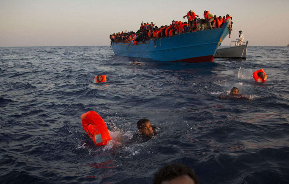 Migrants swim from a crowded boat to reach help during a rescue operation Monday in the Mediterranean Sea near Libya. Five-day-old premature twins were among those picked up by a Doctors Without Borders vessel.