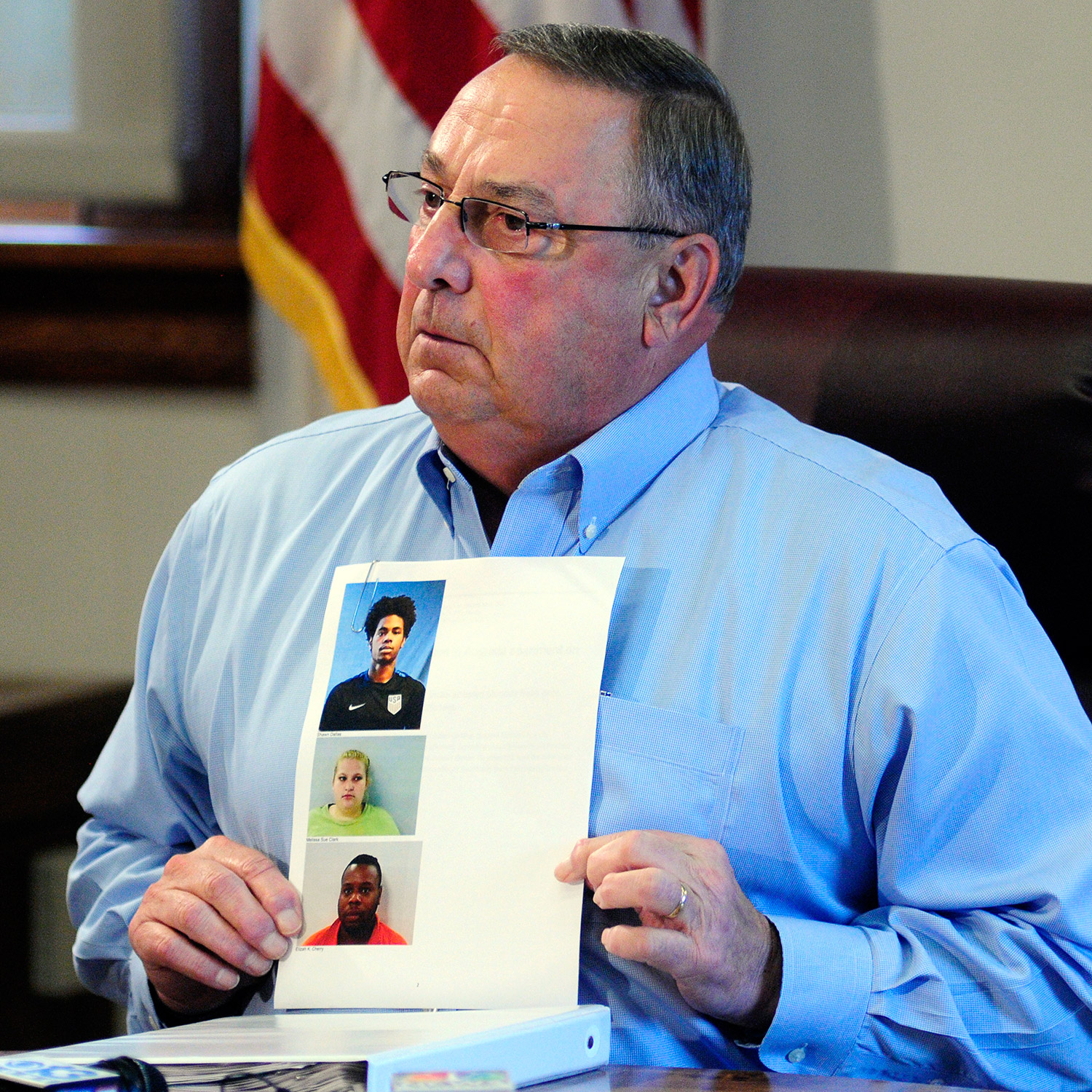 Gov. Paul LePage holds up booking mug shots from a three-ring binder of news releases and articles about drug arrests during a meeting with reporters on Friday in the State House Cabinet room in Augusta.