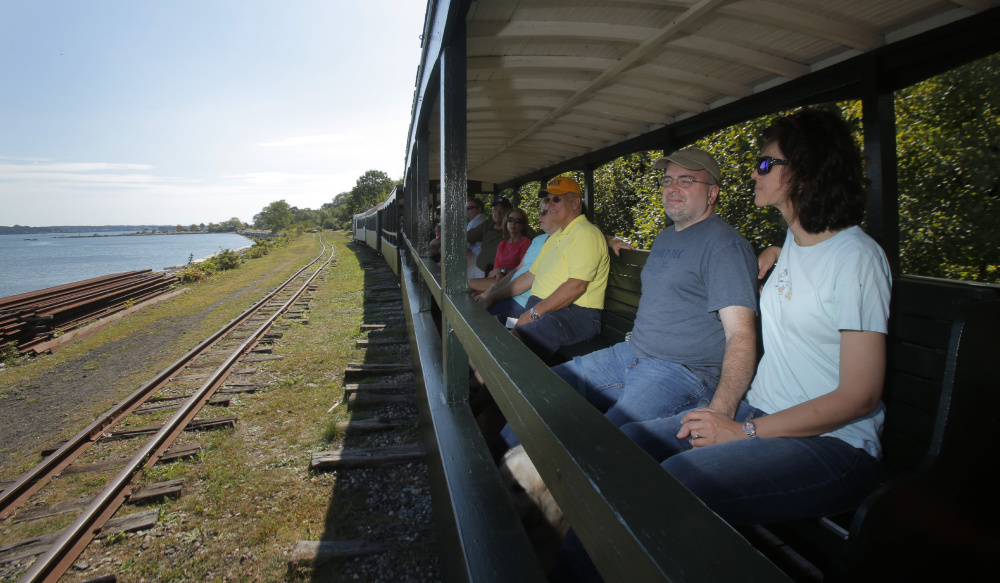 Laura and Franco Chiaramonte and other passengers take in the view as the Maine Narrow Gauge Railroad travels along the Portland waterfront last week. The railroad and museum pull in more than 30,000 visitors a year.