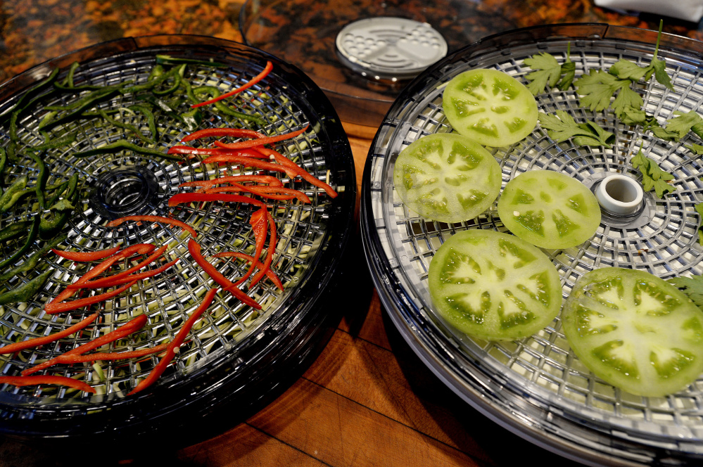 Vegetables in a dehydrator. Drying food saves money, and the end of garden season is a good time to try it.