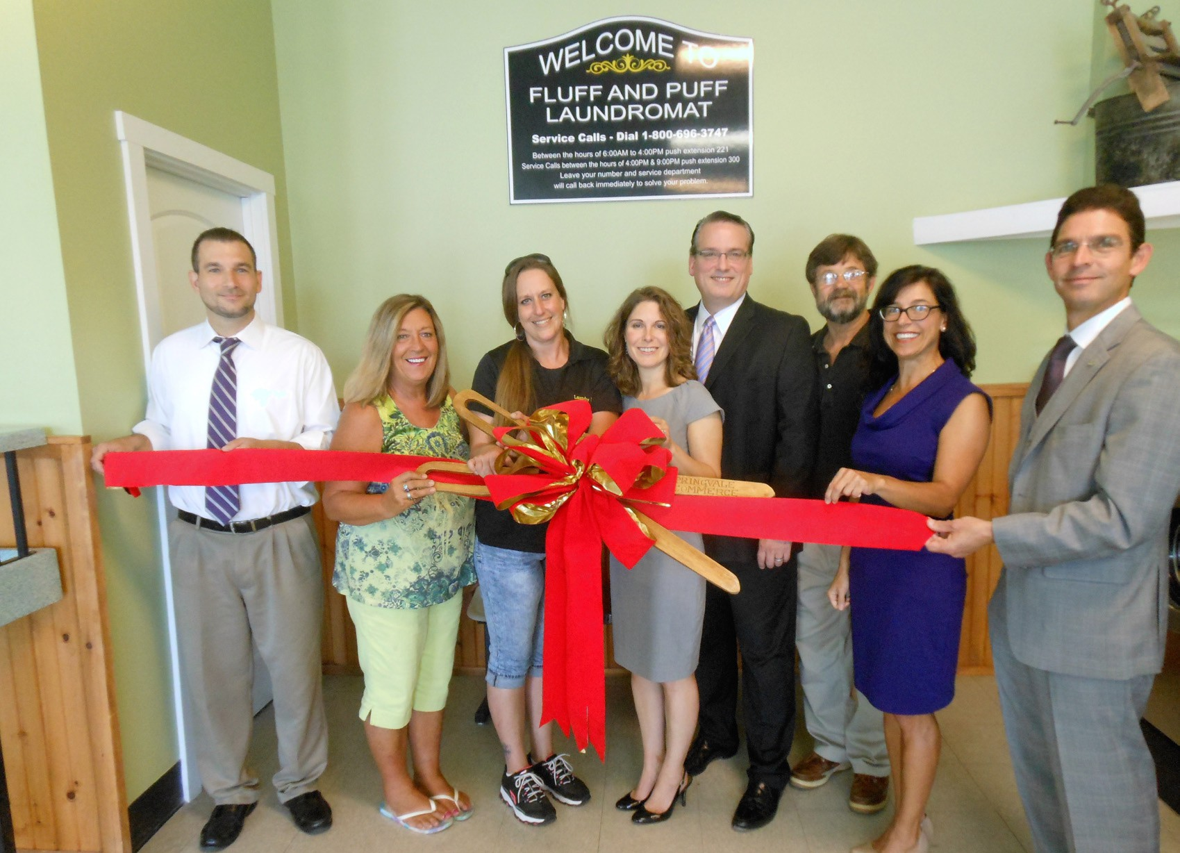 Cutting the ribbon for Fluff-N-Puff Laundry are, from left: Eric Gabois, SIS; Caren Martineau, Bachelder Brothers Insurance; Debbie True, manager of Fluff-N-Puff; Michele Dubois, Ronel J. Dubois Agency; Shawn Babine, Kennebunk Savings; Rick Stanley, Chamber president; Suzanne McKechnie, Investcomm Commercial Group; and Sean Dumont, Edward Jones Investments.