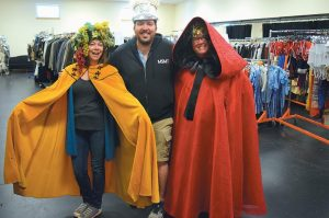 CAROL MARQUIS, Travis Grant and Amy Mussman try on some costumes as they prepare for Saturday's sale.