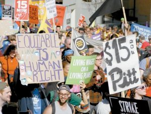 UNION ORGANIZERS, students, and supporters for a $15 an hour wage march through the Oakland section Pittsburgh. Modest income growth for most Americans, strikes by fast-food workers, and the rapid growth of low-paying jobs at the same time middle-income work shrinks have combined to make the minimum wage a top economic issue for the 2016 campaign.