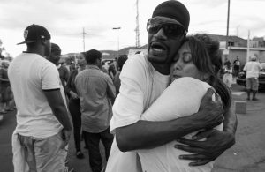 SHAWN LETCHAW hugs a woman named Marie, who didn't give her last name, at the scene where a black man was shot by police earlier in El Cajon, east of San Diego, California, Tuesday.