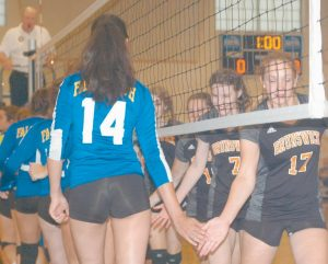 PLAYERS FROM BRUNSWICK and Falmouth meet at the net prior to the start of Tuesday's high school volleyball match in Brunswick.