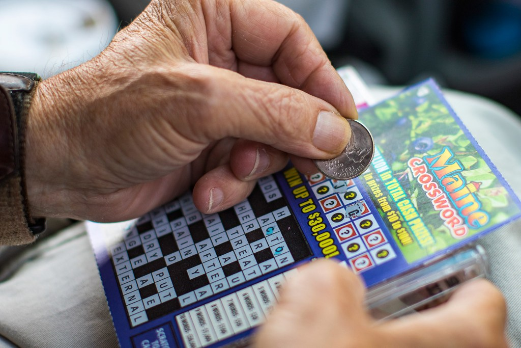 John Walsh scratches a $5 winning lottery ticket in the parking lot of Anania's on Congress Street in Portland. The Maine Lottery set a record for prizes paid to winners in the year that ended June 30.