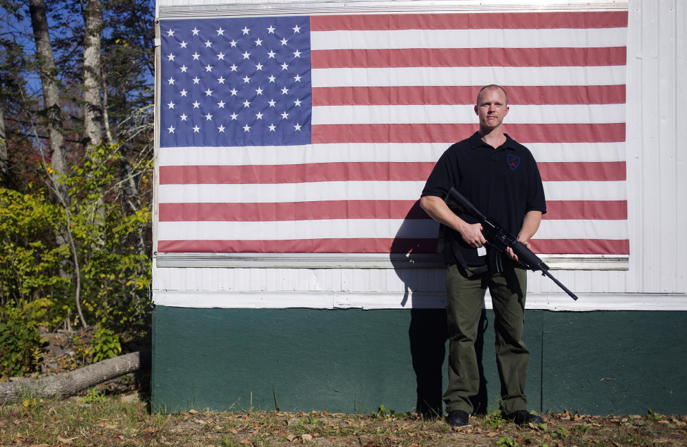 Tim Hendsbee stands with a Windham Weaponry SRC 7.62x39 outside of his small gun shop, HF Firearms, next to his home in Levant.