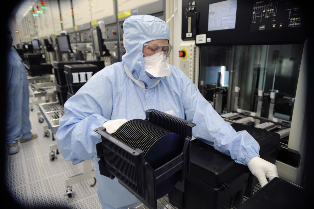 A worker at ON Semiconductor's Pocatello, Idaho, fabrication plant works with wafers in this 2011 photo. The wafers are the foundation of the integrated circuitry that become microchips.