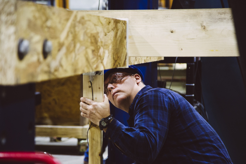 The University of Maine's Advanced Structures and Composites Center technician Walter Morris checks the warp on a piece of lumber from a Norway spruce in Orono in December.