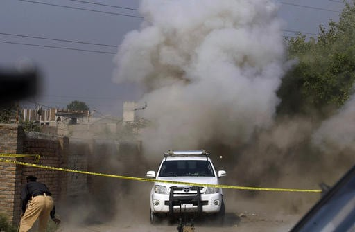 Dust and smoke rises after a bomb is detonated by a bomb disposal squad on the outskirts of Peshawar, Pakistan, Tuesday. Earlier a roadside bomb targeted a police patrol on guard for a polio vaccination team on the outskirts of Peshawar, killing one policeman, according to Superintendent of Police Furqan Bilal, who himself narrowly escaped. //AP WIREPHOTO