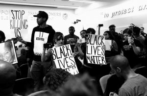 BLACK LIVES MATTER protesters demonstrate inside the board of Police Commissioners meeting in Los Angeles on Tuesday. Los Angeles police released surveillance video Tuesday showing an 18-year-old black suspect running from police while holding what appears to be a gun in his left hand just before he was fatally shot by officers in a death that has generated rowdy protests.