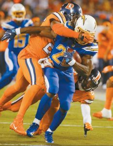 SAN DIEGO CHARGERS running back Melvin Gordon is brought down by Denver Broncos free safety Darian Stewart, above, and cornerback Chris Harris, below, during the second half of an NFL football game on Thursday in San Diego.