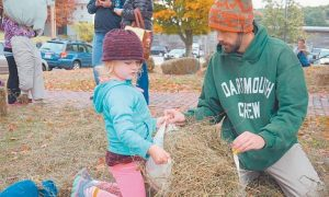 LUCY HELPS HER FATHER Todd Griset stuff a scarecrow during 2015's Autumnfest celebration in Bath.