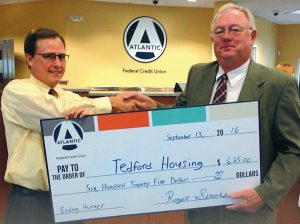 CHRIS LECLERC, left, Topsham's Atlantic Federal Credit Union branch manager, presents a check to Craig Phillips, executive director of Tedford Housing.