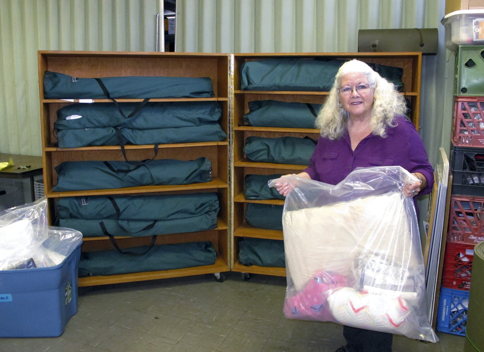 Judi Joy, shelter manager at the Good Samaritan Haven in Barre, Vt., with a set of linens that will be sent to an emergency shelter for the state's homeless population. The center expanded its operations this fall with 14 overflow beds at a church.