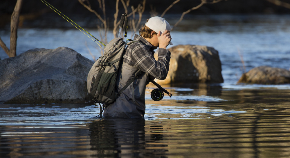 Tucker Van Dusen of Portland blocks the sun while fishing in the Presumpscot River earlier this month. Removing the Sappi dam will revive the ecosystem and open up fishing, he says.