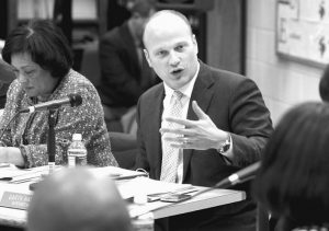 NEW HAVEN Superintendent of Schools Garth Harries, center, speaks at a Board of Education meeting at Hill Regional Career High School in New Haven, Connecticut. After only slightly more than three years, and repeated clashes with members of the city's school board, Harries is stepping down.