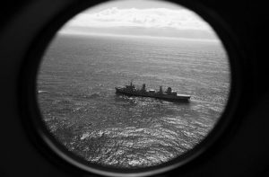 HMAS SUCCESS scans the southern Indian Ocean, near the coast of Western Australia, as a Royal New Zealand Air Force P3 Orion flies over, while searching for missing Malaysia Airlines Flight MH370 in 2014.