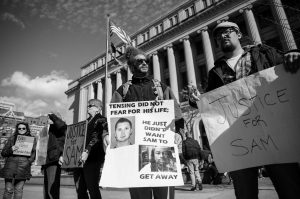 MARK POETTER, center, holds a sign as he protests outside Hamilton County Courthouse on the third day of jury deliberations into Ray Tensing's murder trial on Friday in Cincinnati. Tensing, the former University of Cincinnati police officer, is charged with murdering Sam DuBose while on duty during a routine traffic stop on July 19, 2015.