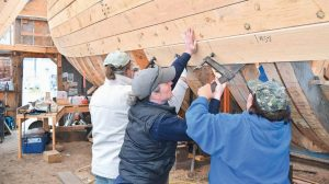 WOMEN HELP HANG a plank on the Virginia, a replica of the first English built ship in America to cross the Atlantic.