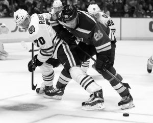 CHICAGO BLACKHAWKS' DENNIS RASMUSSEN and St. Louis Blues' Paul Stastny (26) keep their eyes on the puck during the second period of an NHL hockey game on Wednesday in St. Louis. The Blackhawks won, 2-1, in overtime.