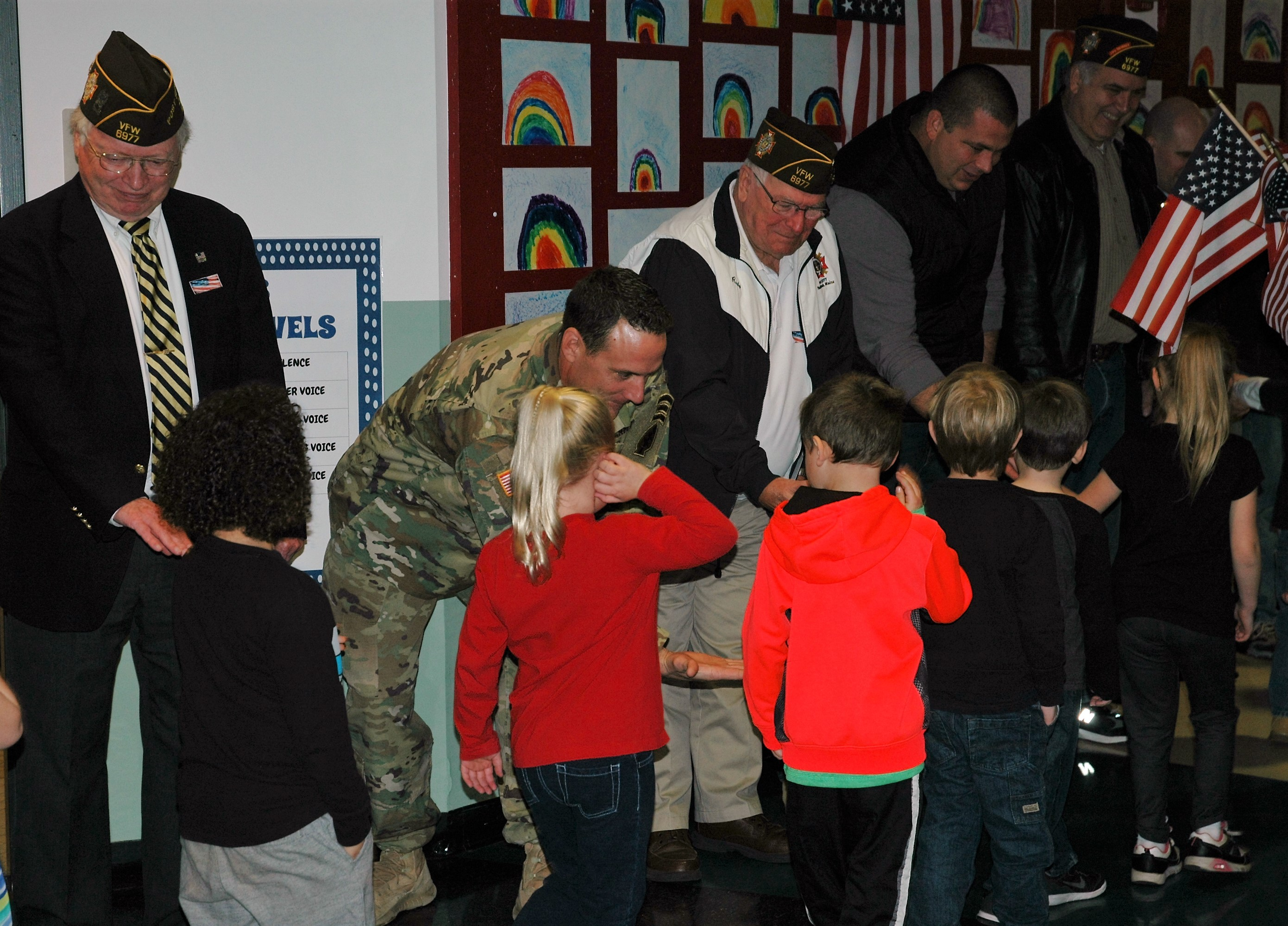 Students shake hands with veterans in the hallway of Wells Elementary School on Thursday as they leave an assembly. LIZ GOTTHELF/Journal Tribune