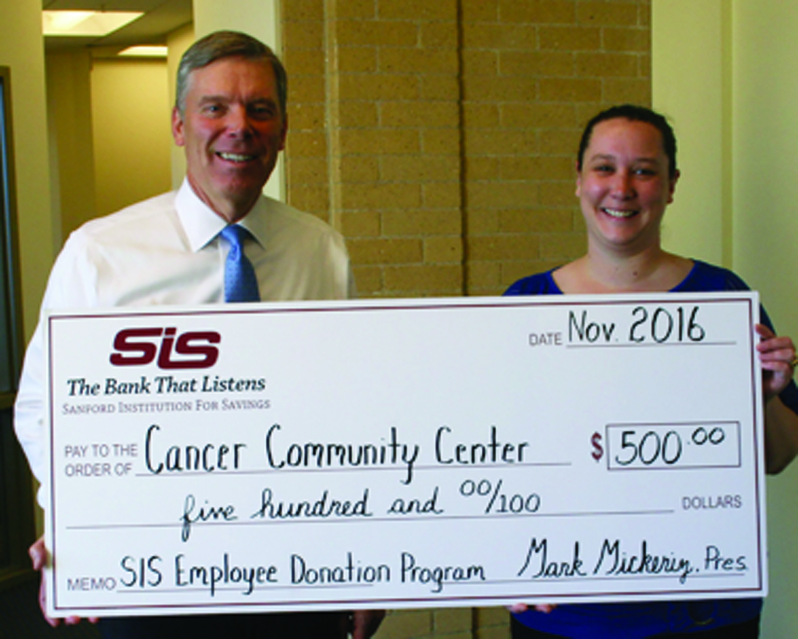 Mark Mickeriz, President and CEO of SIS Bank, left, presents a donation check to Miranda Wyatt, a Collections Clerk at the bank's Main Office  in Sanford.  She chose Cancer Community Center as her favorite nonprofit for the donation. Submitted photo