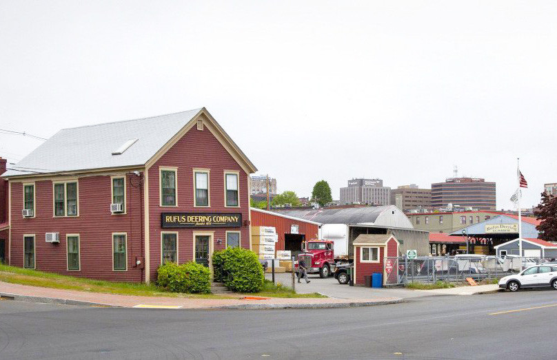 A photo taken in June shows Rufus Deering Lumber Co. on Commercial Street, with downtown Portland in the background. <em>Derek Davis/Staff Photographer</em>
