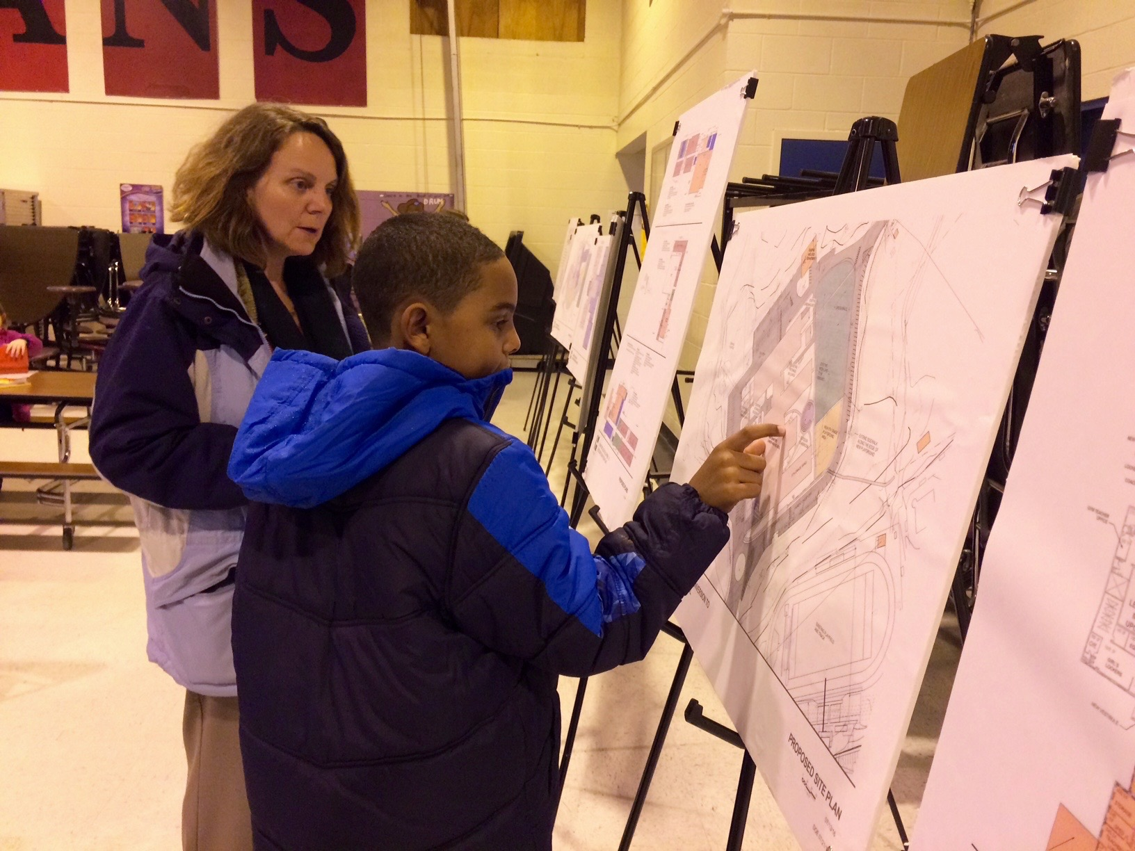 Lynda Butts and her son Micah Butts, a student at Margaret Chase Smith School in Sanford, takes a look at plans for Sanford's elementary and middle school renovation projects at a meeting Tuesday. -TAMMY WELLS/Journal Tribune