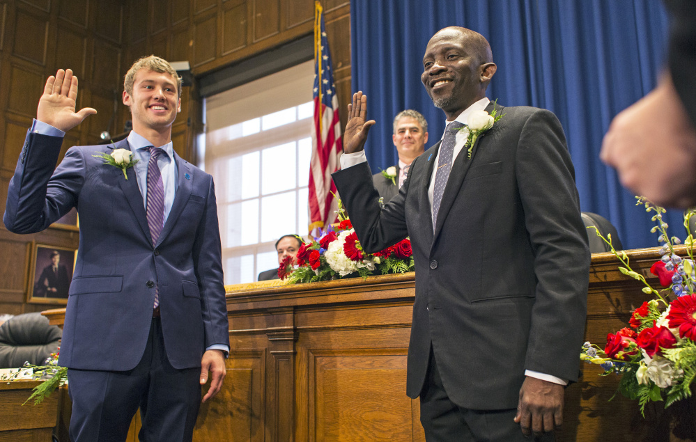 """Newly elected City Councilors Brian Batson, left, and Pious Ali are sworn in during a ceremony Monday at City Hall. It is """"probably the most diverse council in Portland history - maybe Maine history,"""" Mayor Ethan Strimling said. The nine councilors range in age from 25 to 65."""