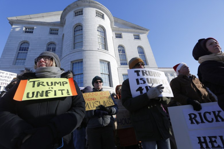 Anti-Trump protesters gather in the cold outside of the Maine State House in advance of Maine's Electoral College vote on Monday, Dec. 19, 2016.