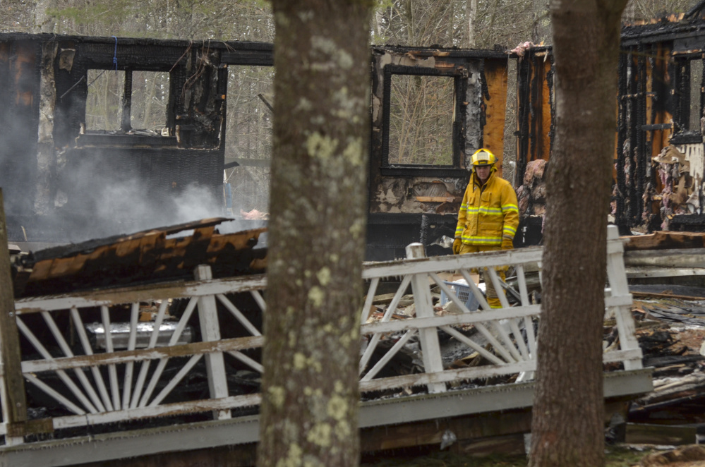 A firefighter walks among the smoldering ashes Monday at the scene of the fatal fire in the Knox County town of Washington.