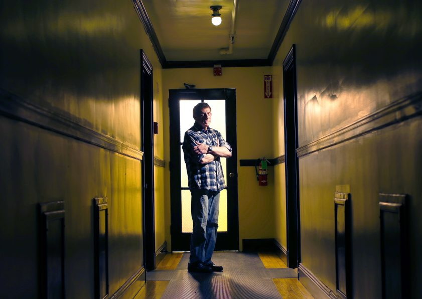 """Jenson Steel, a longtime HIV patient at the India Street clinic who helped others transition to a new health care provider, stands in the corridor outside his West End apartment. The directed transfer of patients to a new facility caused """"emotional trauma,"""" said Steel, 67."""