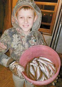 BRADEN CHAPMAN of Bowdoinham holds up his smelt catch earlier this month.