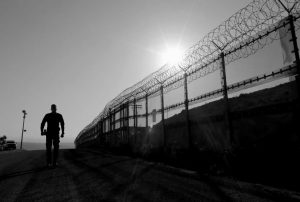 A BORDER PATROL AGENT walks along a border structure in San Diego in 2016. Only about one of every three applicants passes CBP's polygraph, which is barely half the pass rate among law enforcement agencies that provided data to The Associated Press under open-records law requests.