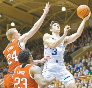 DUKE'S Grayson Allen (3) drives to the basket while N.C. State's Maverick Rowan (24) and Ted Kapita (23) defend during the first half of an NCAA college basketball game in Durham, N.C., on Monday. N.C. State pulled off the upset win.