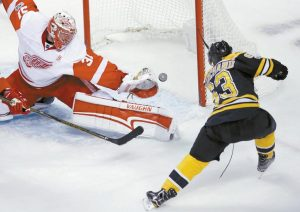 DETROIT RED WINGS goalie Jared Coreau (31) reaches but can't get his glove on the puck on a goal by Boston Bruins left wing Brad Marchand (63) during the first period of an NHL hockey game in Boston on Tuesday. The Bruins won in overtime, 4-3.