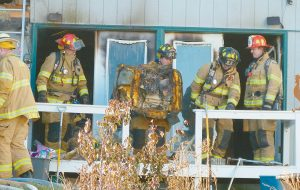 FIREFIGHTERS clear debris following Monday's fire in Harpswell.